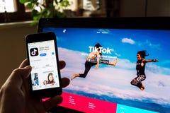 TikTok mobiel video-deelt app bedrijfembleem op het telefoonscherm met Internet-homepage op achtergrond stock foto