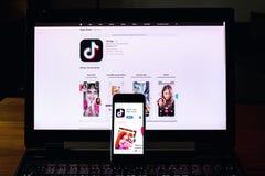 TikTok mobiel video-deelt app bedrijfembleem op het telefoonscherm met Internet-homepage op achtergrond stock fotografie