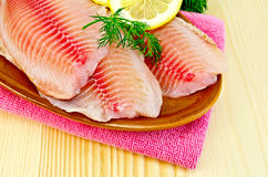 Fillets tilapia in a pottery on a napkin stock image