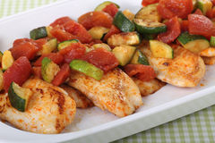 Tilapia Fish Fillets. Fried tilapia fish fillets covered with zucchini and tomato royalty free stock images