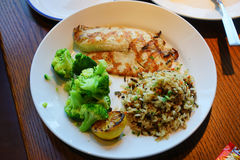 Tilapia fish and a lemon wedge and served with wild rice and couscous and broccolini. Stock Image