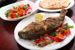 Tilapia fish meal. Tilapia fish with salad on table stock images