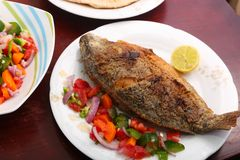 Tilapia fish meal. Tilapia fish with salad on table stock photo