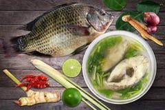 Tilapia och kokt tilapiafisk i klar bunke och ingredienscurry på träbakgrundsTom-sötpotatis-plommoner thai ord, styckskivafisk Arkivbilder