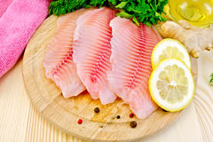 Tilapia with oil and lemon on board stock images