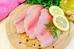 Tilapia with oil and lemon on light board royalty free stock photography