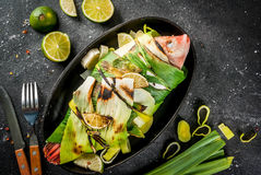 Tilapia roasted on grill in leeks. Gish. seafood. Asian and Eastern cuisine. Red tilapia roasted on a grill in leaves of leeks with slices of lime, herbs and royalty free stock photos