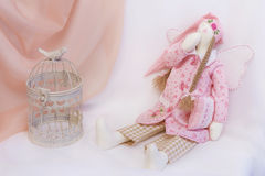 Tilda doll in pink and a toy cage Stock Images