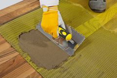 Tile adhesive on wooden floor Royalty Free Stock Photos