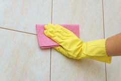 Tile cleaning. With gloves and rag Stock Photo