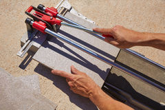 Tile cutter machine with mason hands cutting Stock Image