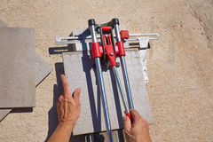 Tile cutter machine with mason hands cutting Stock Photos