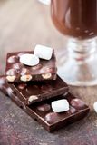Tile dark chocolate with hazelnuts, marshmallows, drink Royalty Free Stock Photo