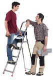 Tile fitters having a conversation. Whilst up a ladder royalty free stock images