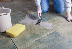 Tile Grout Repair. A man repairing the grout on a tile floor Stock Images