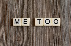 Tile letters spelling the words `Me Too`. Square tiles with lettering spelling a word on a wood background stock photos
