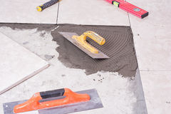 Tile. Notched trowel, spacers and prepared setting compound for tile royalty free stock photo