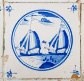 Tile with painting of sailing ships. Delft blue and white tile with the painting of sailing ships royalty free stock image