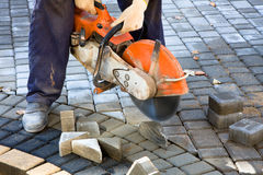 Tile paving. Working sawing pieces of paving slab on, Man cutting control groove in concrete paving stock images