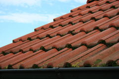 Tile roof. Covered with red tiles, overgrown with moss Royalty Free Stock Photography