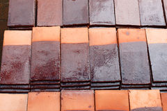 Tile roof. Roof tiles are designed mainly to keep out rain, and are traditionally made from locally available materials such as clay or slate Stock Image