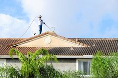 Tile roof cleaning, FL. Worker is cleaning the tiles on the roof in South Florida Royalty Free Stock Images