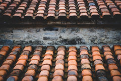 Tile roof. Old damaged ceramic tile roof background. Tinted and filtered photo Stock Photos