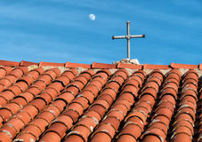 Tile roof and rustic cross on historic church Stock Images