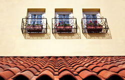 Tile roof and windows. European style tile roof and windows with flowerpots royalty free stock photo