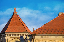 Tile Roofs. Six Sided Orange Tile Turret Roof On Top of an Ornately Designed Brown Building Next to a Triangular Shaped Roof Royalty Free Stock Images