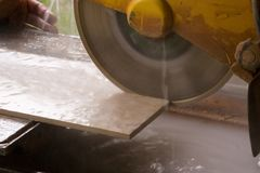 Tile saw cutting tile. Water lubricated tile saw cutting a tile Royalty Free Stock Photos