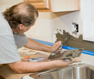 Tile Setter Applying Mortar. To drywall in preparation for tiling it Royalty Free Stock Photos