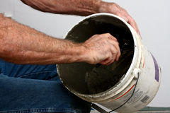 Tile setter stirring container of thin set Royalty Free Stock Photography