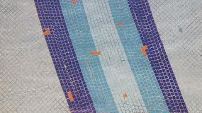 Tile texture. Blue small size ceramic tile under water on the bottom of the pool. Horizontal picture with dark blue and blue vertical lines and orange dots Royalty Free Stock Image
