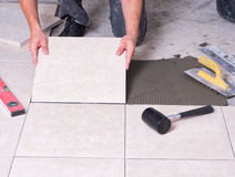 Tile. R installing ceramic s on a floor Stock Images