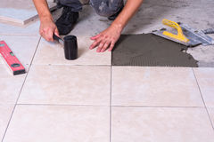 Tile. R installing ceramic s on a floor Royalty Free Stock Photo