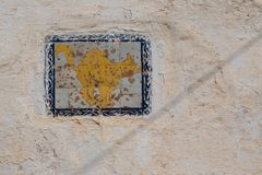 Tile on the wall of a house, Morocco. Old structured and weathered wall of a house with a tile, motive of a cat in yellow color and blue frame. Kasbah de Oudaias stock photography