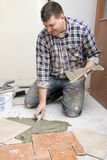 Tile work. A smiling construction worker putting on new floor tiles. Tile work stock images