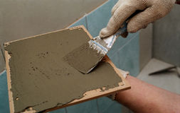Tile work. A man working on installing tile Royalty Free Stock Photos