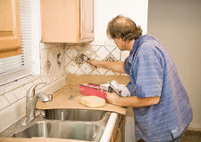 Tile Work - Applying Grout. Middle aged tile-setter applying grout to kitchen tiles Royalty Free Stock Photography