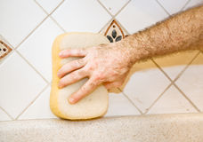 Tile Work - Wiping Grout. Worker's hand using a sponge to wipe fresh grout from ceramic tile Stock Photo