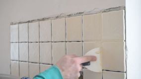 Tile worker filling gaps between tiles with grout stock video
