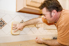 Tile Worker Wipes Grout. Tile worker wiping grout from a newly tiled kitchen wall.  Focus on hand with sponge Royalty Free Stock Photo