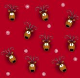 Tileable Reindeer Heads. A tileable background pattern featuring reindeer heads on red with snowflakes Stock Image