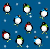 Tileable Xmas Penguins. A tileable background pattern featuring penguins dressed in scarves on blue with white snowflakes Royalty Free Stock Photo