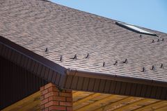Tiled brown roof of new house with overflow, protection, from snow and fronton made of siding Stock Photos