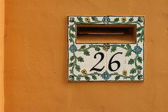 Tiled ceramic letterbox for home. Against orange wall Royalty Free Stock Photography