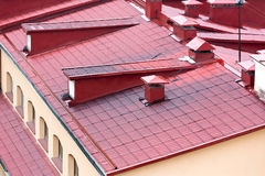 Tiled red metal roof with chimneys and windows Stock Images
