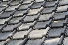 Tiled roof. Roof detail with old fashioned ceramic black tiles, one is damaged stock image