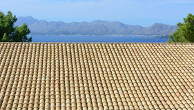 Tiled roof and blue bay. With mountains. Mallorca, Balearic islands, Spain Royalty Free Stock Images